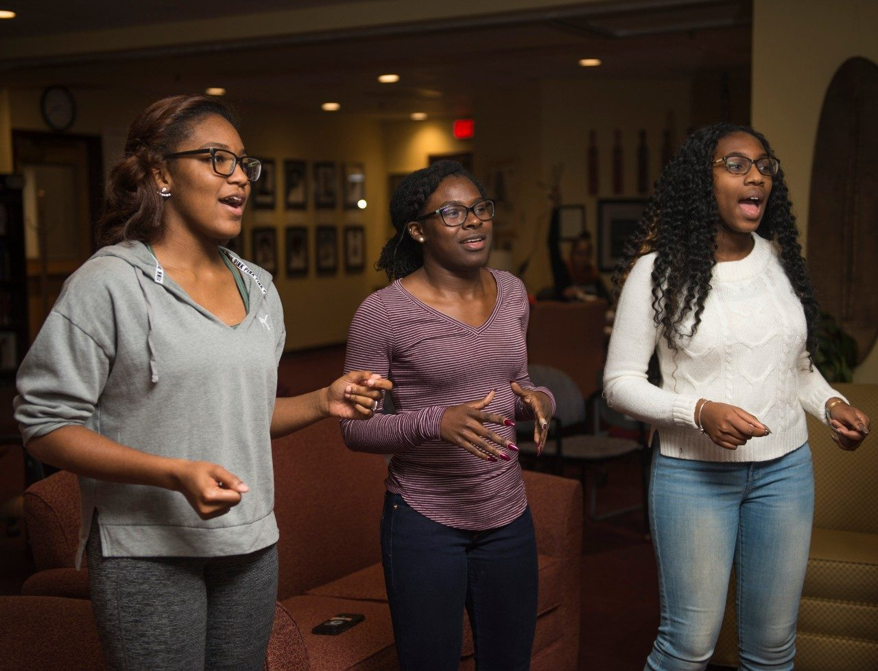 A'via Linton, Lauren Brown, and Michelle Ya Diul, Virginia Tech students and members of the Enlightened Gospel Choir, rehearse in the Black Cultural Center.